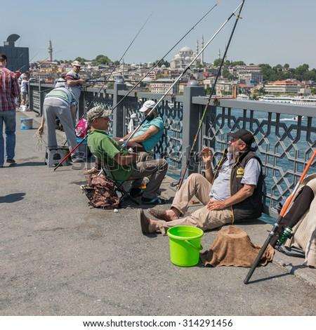ISTANBUL, TURKEY - JUNE 20: Unidentified Turkish fishermen fishing on Galata Bridge on June 20, 2015 in Istanbul, Turkey - stock photo