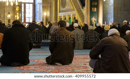 ISTANBUL, TURKEY - 22 MARCH, 2013: Muslim men praying in Yeni Cami (New Mosque) interior. New Mosque is located in the Eminonu quarter of Istanbul, Turkey. - stock photo