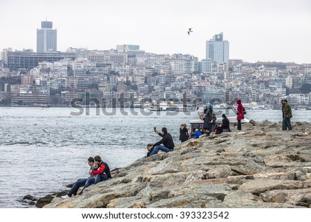 ISTANBUL, TURKEY - MARCH 20, 2011: Tourists and local People relaxing near Bosphorus strait on Uskudar district of Istanbul city. - stock photo