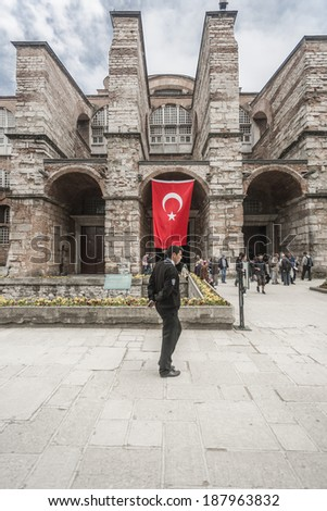 ISTANBUL, TURKEY - MAY 19, 2011: A guard stands at the entrance of the Ayia Sofia museum, in Sultan Ahmet, and makes sure everything is normal in the surrounding area and with all the visitors. - stock photo