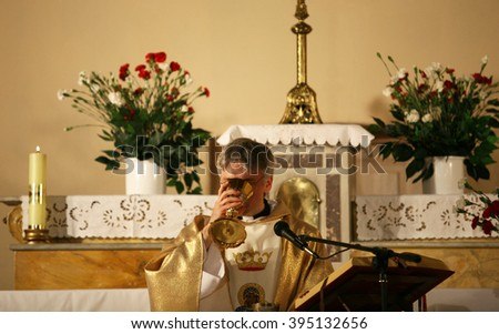 ISTANBUL, TURKEY - MAY 2: Interior of Czestochowa's Mother Mary Church on May 2, 2009 in Istanbul, Turkey. Priest, praying to God consecration the bread and wine.  - stock photo
