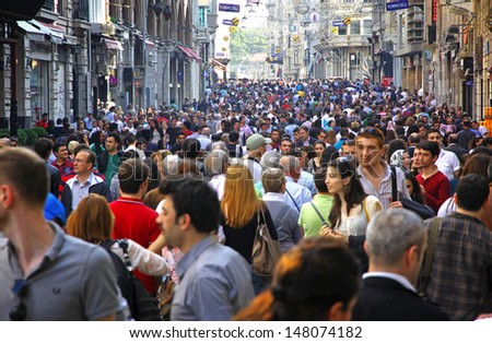 ISTANBUL, TURKEY - MAY 5: People walking on Istiklal Street on May 5, 2012 in Istanbul, Turkey. It is the most famous street in Istanbul, visited by nearly 3 million people in a single weekends day - stock photo