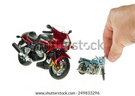 Istanbul, Turkey - November 14, 2014: Collectible plastic model Moto Guzzi Le Mans on white background with a little toy and human hand. - stock photo