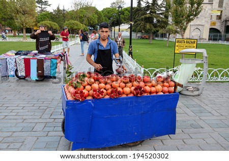 ISTANBUL TURKEY SEPT 28: Young man sells pomegranate juice for to live in down town Istanbul on september 28 2013. Pomegranate juice is one of the most popular in Turkey - stock photo