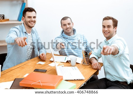 IT company. Young programmers working with laptop. Nice office interier. Professional coders looking and pointing at camera, and smiling - stock photo
