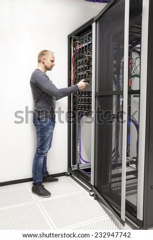 IT consultant build network rack in datacenter - stock photo
