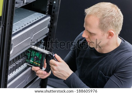 IT Consultant replace SAN hard drive - stock photo