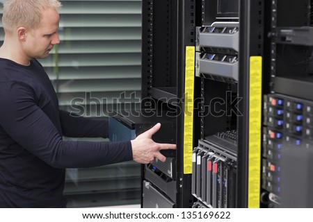 It engineer / consultant install / inserts a router / switch in a rack. Shot in a data center. - stock photo