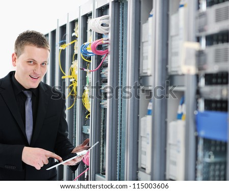 IT engineer in network server room using tablet computer - stock photo