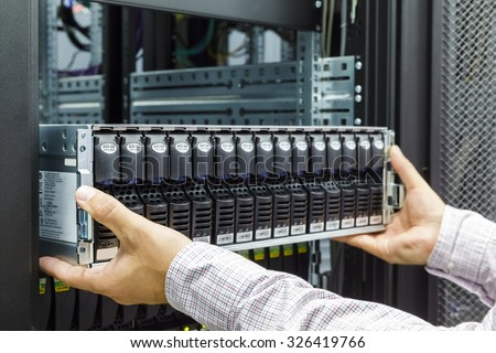 IT Engineer installs equipment in the rack in datacenter - stock photo
