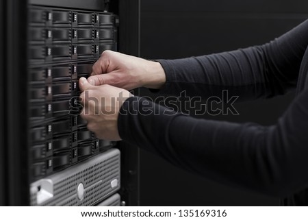 It engineer / technician working in a data center. This enclosures is a SAN (storage area network) and servers bellow. - stock photo