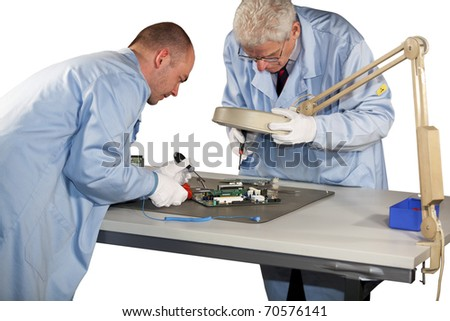 IT engineers doing repairs on a motherboard - stock photo