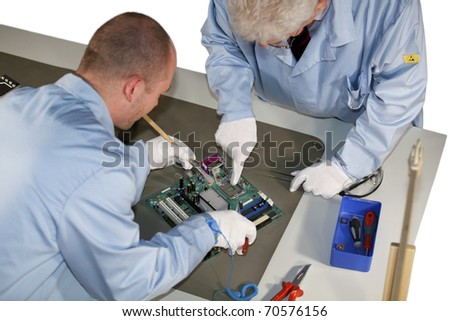 IT engineers doing repairs on a motherboard