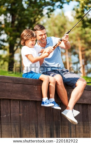 It is a big fish! Happy father and son fishing together while sitting on quayside - stock photo