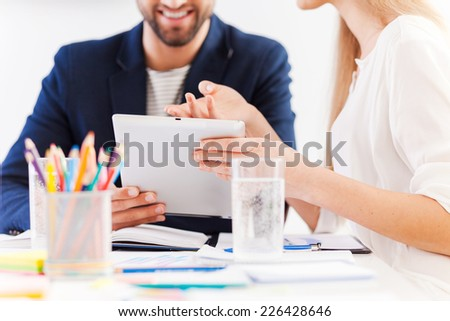 It is a great idea! Close-up of two confident business people in smart casual wear sitting at the table together and discussing something while looking at the digital tablet  - stock photo