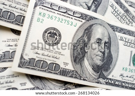 It is a lot of 100 dollar bills with Benjamin Franklin's face - stock photo