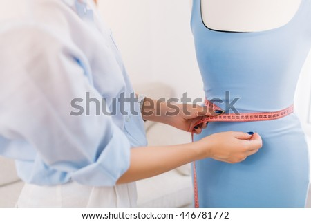 It is a picture where the main thing is concentrated on hands of a girl who makes fitting of dress on the mannequin. This picture is made in workshop studio.
