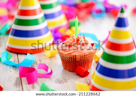 It is a special day. Image of a delicious cupcake with a candle surrounded by party hats and confetti on the background