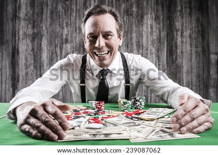 It is all mine! Happy senior man in shirt and suspenders sitting at the poker table and embracing chips and money laying on it  - stock photo
