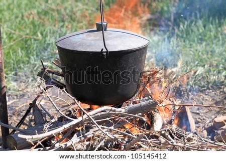 It is fish soup preparation on a bonfire - stock photo