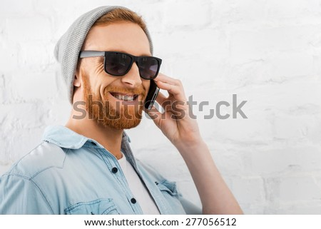 It is great to hear from you! Cheerful young bearded man talking on the mobile phone and smiling while standing against brick wall - stock photo