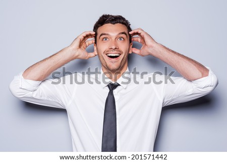 It is just unbelievable! Happy young man in shirt and tie touching head with hands and smiling while standing against grey background  - stock photo