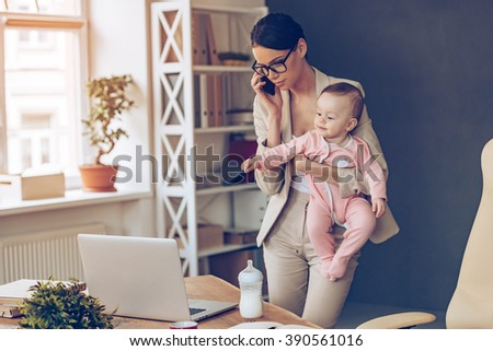 It is not easy to be a working mom! Young beautiful businesswoman talking on mobile phone and looking at laptop while standing with her baby girl at her working place - stock photo