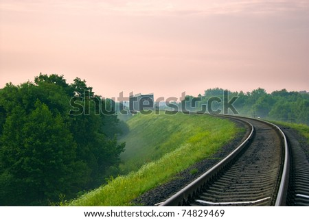 It is receding into the distance railroad and the bridge in the morning mist. Sunrise.