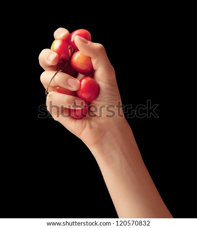 It is red a yellow sweet cherry lies in a hand of the young girl