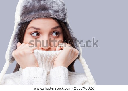 It is so cold. Frozen young women covering face with turtleneck while standing against grey background - stock photo