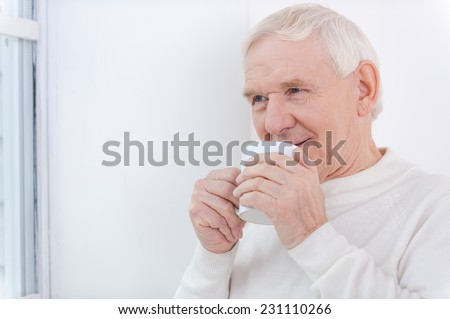 It is so warm at home!  Cheerful senior man holding cup of coffee and looking away while standing near the window - stock photo