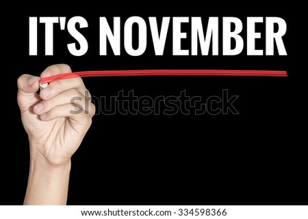 It November word writting by men hand holding highlighter pen with line on black background - stock photo