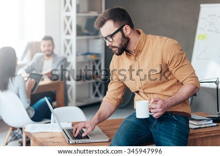 IT professional at work. Confident young man working on laptop while his colleagues talking in the background - stock photo