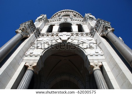 It's a Basilic situated in Lyon, France, from the bottom . It's white,  old religious construction , with specific detailes, use a baroque style.In the background there is the blue sky. - stock photo