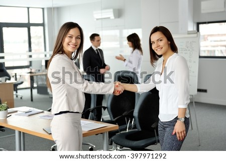 It's a deal!  Business women handshaking. Their colleagues on a background. - stock photo