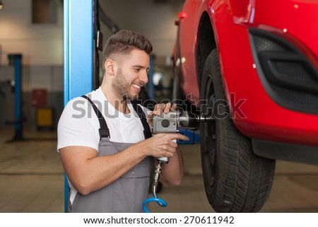 It's Easy To Change Car Wheel With Right Tool. Car mechanic changing the wheel with an impact wrench. Waist up shot in auto repair shop. - stock photo