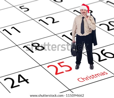 It's finally christmas - happy businessman standing on december calendar - stock photo