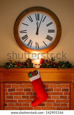 It's just past midnight on Christmas Eve / Day and Santa has been, gifts are in the stocking hanging over the fireplace, as candles burn on the mantlepiece surrounded by a holly and ivy garland. - stock photo