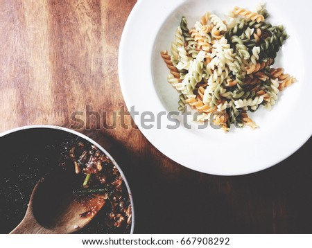 It's time for pasta lovers. The picture of boiled fusilli on white plate and bolognese sauce on black bowl above wooden table.  soft tone