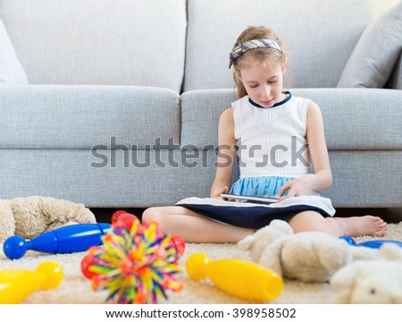 It's time to clean up your toys! Little girl playing with tablet pc, don't want to do the cleaning. - stock photo