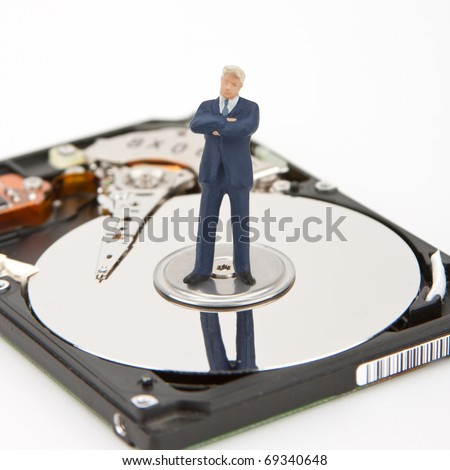 IT security. Businessman on computer hard drive - stock photo
