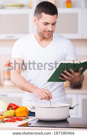 It tasted so good! Handsome young man tasting soup from the pan and smiling while standing in the kitchen - stock photo