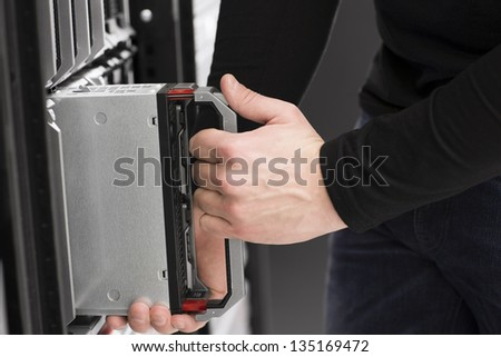 IT technician / engineer install / removes / replace a blade server in a data center. - stock photo