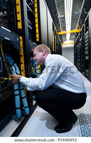 IT technician working on network servers and cables - stock photo