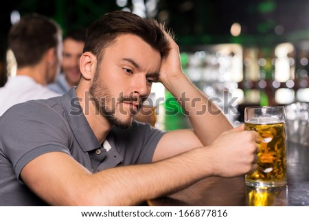 It was a hard day. Depressed young man drinking beer in bar and holding hand in hair - stock photo