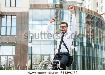 It was successful day! Low angle view of cheerful young businessman keeping arms raised and expressing positivity while riding on his bicycle - stock photo