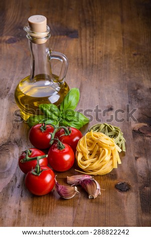Italian and Mediterranean food ingredients on wooden background.Cherry tomatoes pasta, basil leaves and carafe with olive oil - stock photo