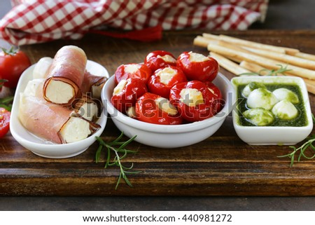 Italian appetizer antipasti made dish - ham, cheese, peppers - stock photo