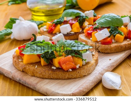 Italian Appetizer Bruschetta with roasted Pumpkin, Red Bell Pepper, Spinach, Garlic and Feta Cheese - stock photo