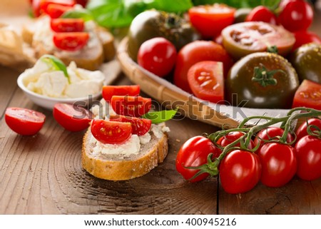 Italian appetizer - bruschetta with tomatoes, feta cheese and basil, on rustic wooden background, selective focus - stock photo